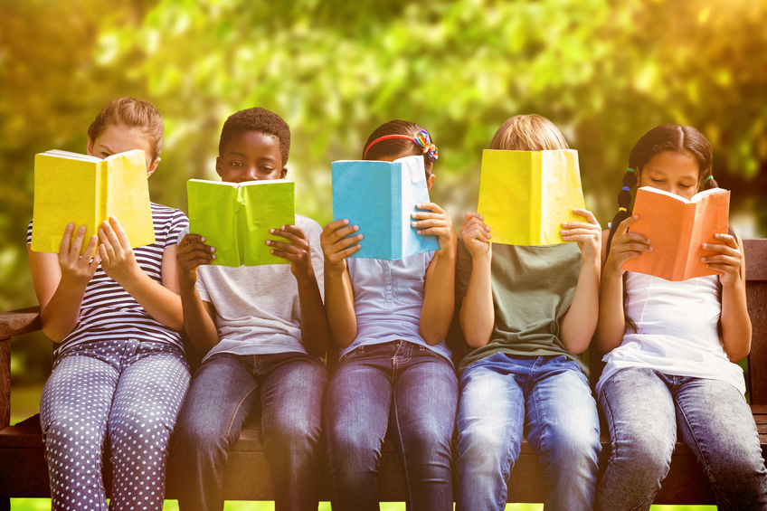44598687 - children reading books at park against trees and meadow in the park